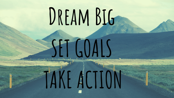 Dream Big, Set Goals, Take Action with an empty road leading to mountains in the distance.